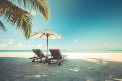 Exotic travel destination, loungers and umbrella under palm leaf. Luxurious tropical beach landscape. Beautiful tropical sunset scenery, two sun beds, loungers stock images