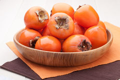 Exotic tropic orange fruits persimmon in plate Stock Image