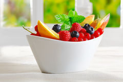 Exotic tropical fruit dessert. In a decorative boat-shaped bowl with sliced orange and an assortment of ripe berries Royalty Free Stock Photos