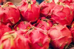 Exotic tropical fruit, dragon fruit or pitaya display for sell in market. Selective focus shot. image may contain noise and grain due to available light shot Royalty Free Stock Photo