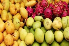 Exotic tropical fruits mango, dragon fruit closeup on a market. Exotic tropical fruits mango, dragon fruit closeup on a market, top view stock images