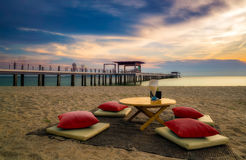 Exotic twilight dining seat on the beach. Royalty Free Stock Images