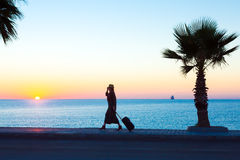 Exotic Vacation Silhouette of Female pulling Travel Suitcase on Seafront Stock Photography