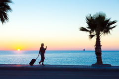 Exotic Vacation Silhouette of Female pulling Travel Suitcase on Seafront. Alley Luminous Sunrise on Background tropical Tree Royalty Free Stock Photos