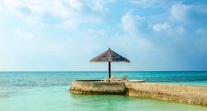 An exotic view of a palm tree umbrella on a cape overlooking the sea, Maldives Royalty Free Stock Photo