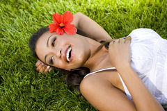 Exotic woman. Beautiful exotic woman with a red hibiscus Stock Image