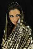 Exotic woman in golden drapery. Stock Photo