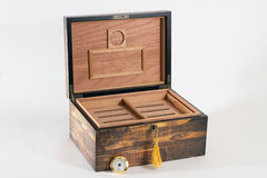 Exotic wood cigar humidor. Empty exotic wood cigar humidor with open lid and key against white background Stock Images
