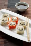 Exotisch japanische Meeresfrüchte, Rolle und Essstäbchen liegen auf einer weißen Platte Sojabohnenöl souce stockfotografie