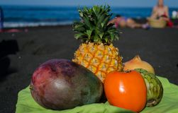 Exotische Früchte auf dem schwarzen Sandstrand in den Kanarischen Inseln lizenzfreie stockfotos