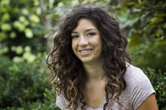 Exotische schauende junge Frau in der grünen Einstellung Stockfoto