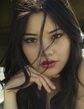 Exotische schmollende Augen auf reizvoller asiatischer Frau Stockbild