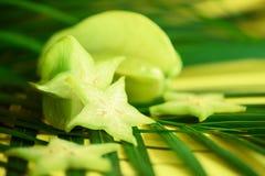Exotische sterfruit of averrhoacarambola over tropische groene palmbladen op gele achtergrond De ruimte van het exemplaar Zes ver Stock Foto's