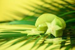 Exotische sterfruit of averrhoacarambola over tropische groene palmbladen op gele achtergrond De ruimte van het exemplaar Zes ver Stock Afbeelding