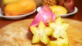 Exotische vruchten op de lijst 4k, roteren carambola en Dragonfruit, besnoeiing in stukken, op een scherpe raad stock videobeelden