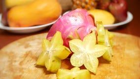 Exotische vruchten op de lijst 4k, roteren carambola en Dragonfruit, besnoeiing in stukken, op een scherpe raad stock video