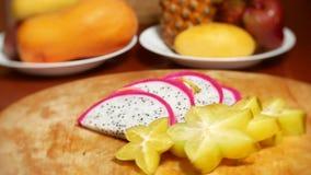 Exotische vruchten op de lijst 4k, roteren carambola en Dragonfruit, besnoeiing in stukken, op een scherpe raad stock footage