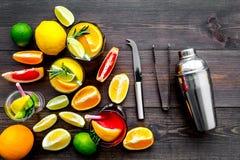 Exotischer Fruchtcocktail der Mischung mit Alkohol Schüttel-Apparat und Sieb nahe Zitrusfrüchten und Glas mit Cocktail auf dunkle Stockfoto