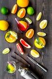 Exotischer Fruchtcocktail der Mischung mit Alkohol Schüttel-Apparat und Sieb nahe Zitrusfrüchten und Glas mit Cocktail auf dunkle Lizenzfreies Stockfoto