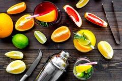 Exotischer Fruchtcocktail der Mischung mit Alkohol Schüttel-Apparat und Sieb nahe Zitrusfrüchten und Glas mit Cocktail auf dunkle Stockfotos
