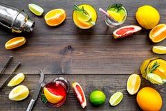 Exotischer Fruchtcocktail der Mischung mit Alkohol Schüttel-Apparat und Sieb nahe Zitrusfrüchten und Glas mit Cocktail auf dunkle Lizenzfreie Stockfotografie