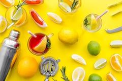 Exotischer Fruchtcocktail der Mischung mit Alkohol Schüttel-Apparat und Sieb nahe Zitrusfrüchten und Glas mit Cocktail auf Gelb Lizenzfreies Stockbild