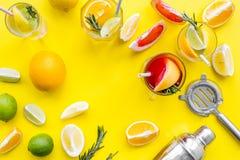 Exotischer Fruchtcocktail der Mischung mit Alkohol Schüttel-Apparat und Sieb nahe Zitrusfrüchten und Glas mit Cocktail auf Gelb Lizenzfreie Stockfotografie