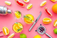 Exotischer Fruchtcocktail der Mischung mit Alkohol Schüttel-Apparat und Sieb nahe Zitrusfrüchten und Glas mit Cocktail auf Rosa Stockfoto