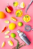 Exotischer Fruchtcocktail der Mischung mit Alkohol Schüttel-Apparat und Sieb nahe Zitrusfrüchten und Glas mit Cocktail auf Rosa Lizenzfreies Stockbild