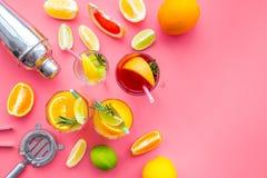 Exotischer Fruchtcocktail der Mischung mit Alkohol Schüttel-Apparat und Sieb nahe Zitrusfrüchten und Glas mit Cocktail auf Rosa Lizenzfreie Stockbilder