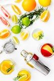 Exotischer Fruchtcocktail der Mischung mit Alkohol Schüttel-Apparat und Sieb nahe Zitrusfrüchten und Glas mit Cocktail auf Weiß Stockfotografie