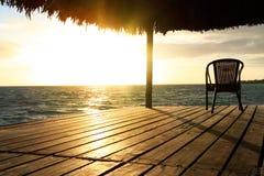 Exotischer hölzerner Gazebo und Stuhl auf dem Strand bei Sonnenuntergang oder Sonnenaufgang Hintergrund einer Küste mit Sitz, sti stockfotos