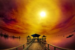 Exotischer Pier und Ozean unter bewölktem Sonnenaufgang Stockfotos