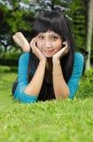 Exotisches asiatisches Mädchen, das lächelt und sich hinlegt Lizenzfreie Stockfotos