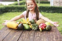 Exotisk frukt på trätabellen Sommarbakgrund med att skratta den lyckliga flickan Arkivbilder