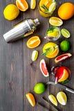 Exotisk fruktcoctail för blandning med alkohol Shaker och filter nära citrusfrukter och exponeringsglas med coctailen på mörkt tr fotografering för bildbyråer