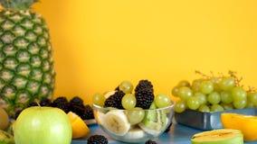 Exotisk fruktsallad som göras från bananer, kiwi, druvor och bär lager videofilmer