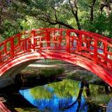 Exotisk krökt röd orientalisk bro som förbiser reflekterande vatten Arkivbild