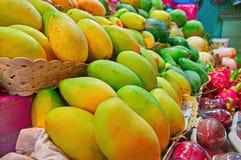 Exotiska frukter för begreppsgatahandel Tropiska frukter på räknare av en gata shoppar Mogen gul mango och drakefrukt Arkivbilder