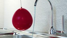 Expérience d'électricité statique avec de l'eau le ballon et l'eau du robinet Images stock