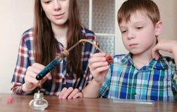 Expériences sur la chimie à la maison Le garçon et sa maman chauffent le tube à essai avec le liquide bleu sur la lampe brûlante  Photographie stock libre de droits
