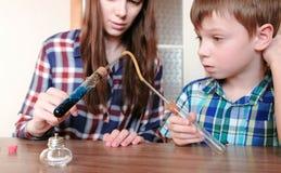 Expériences sur la chimie à la maison Le garçon et sa maman chauffent le tube à essai avec le liquide bleu sur la lampe brûlante  Images stock