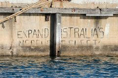 `Expand Australia`s Merchant Fleet` graffiti in South Australia. Graffiti stating `Expand Australia`s Merchant Fleet` on the wharf at Port Adelaide in Adelaide stock photography