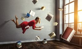 Expanding the imagination. Mixed media. Relaxed woman levitates in room full of flying books. Mixed media royalty free stock images