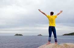 Expanse. The young man costs(stands) on a stone at the sea having stretched hands Royalty Free Stock Photography