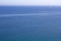 Expanse of blue water of sea with a white sailboat to horizon. Panoramic Royalty Free Stock Photography