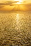 Expanse of ocean at sunrise with sunrays and clouds. With ine of sun reflected in water stock photo
