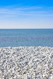 Expanse of white gravel on the sea coast with calm sea on backgr. Ound stock images