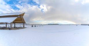 Expansief landschap dat met onder sneeuw onder een bewolkte blauwe hemel in de winter wordt bedekt stock afbeeldingen