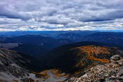 Expansief landschap met bergranden en gele bomen onder onweershemel royalty-vrije stock foto's